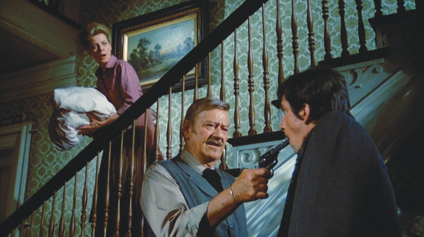"""Make like that's a nipple."" J.B. Books (John Wayne) makes clear his displeasure with a proposition from a newspaper man (Rick Lenz) as his landlady (Lauren Bacall) looks on with horror in ""The Shootist."""