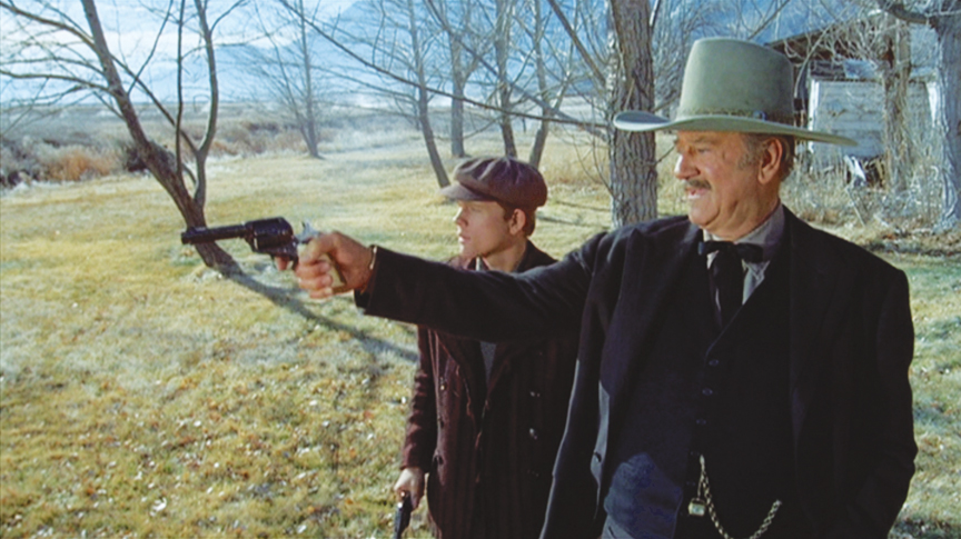J.B. Books (John Wayne) gives Gillom Rogers (Ron Howard) a shooting lesson.