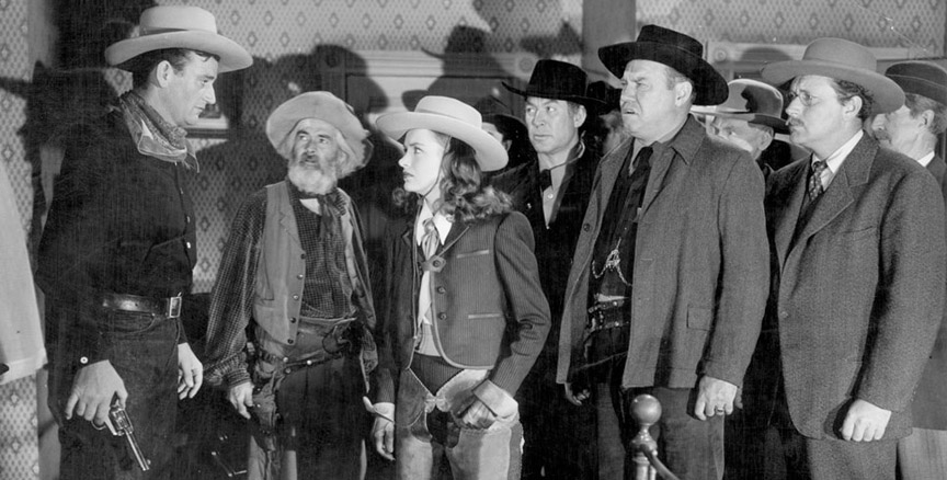"Things look bad for Rocklin, at a murder scene more crowded than a Charlie Chan drawing room. From left: John Wayne, George ""Gabby"" Hayes, Ella Raines, Ward Bond, Emory Parnell and Donald Douglas."